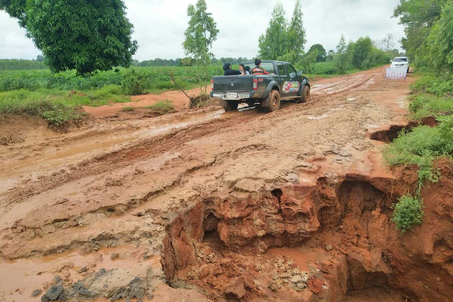 ็Heavy rain washed away this section of road at Phan Charoen village in Chumphuang district of Nakhon Ratchasima province. (Photo by Prasit Tangprasert)