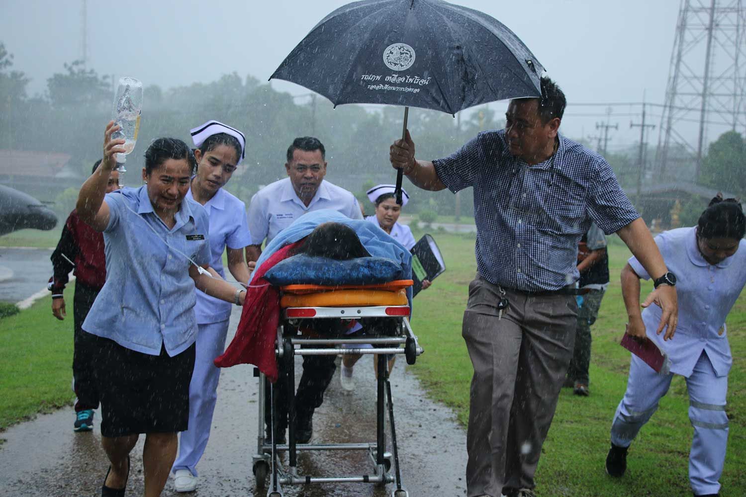 A woman with pregnancy complications is taken to a helicopter in pouring rain at a remote village near Thungyai Naresuan Wildlife Sanctuary in Sangkhla Buri district, Kanchanaburi, on Wednesday aftrnoon. The 33-year-old woman was airlifted safely to Sangkhla Buri Hospital. (Photo by Piyarat Chongcharoen)