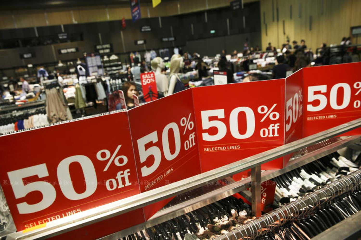 Discount signs attract shoppers at a Bangkok department store. (File photo)