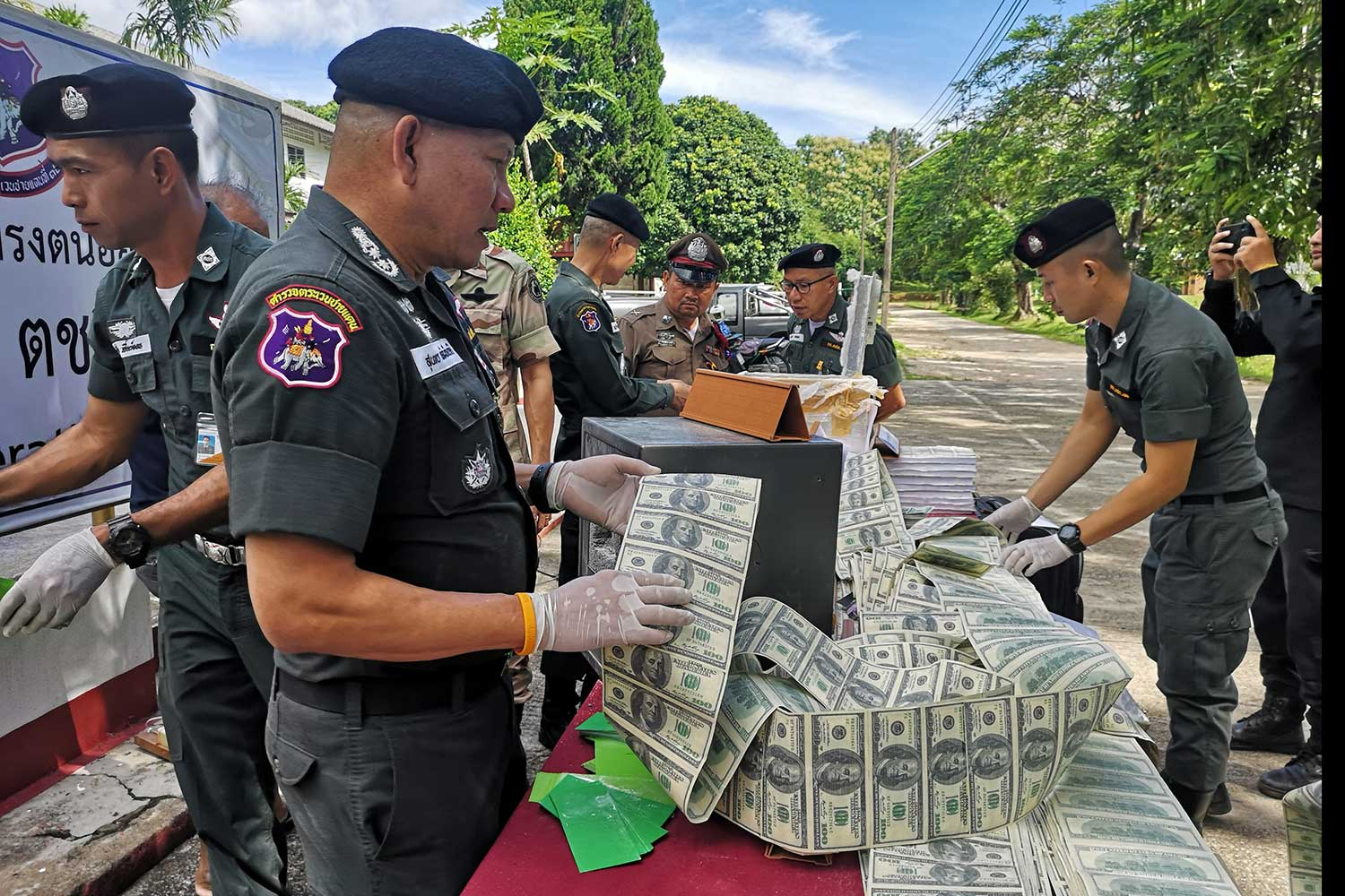 Counterfeit US$100 banknotes are seized at a house in Muang district, Chiang Rai,  and the 54-year-old house owner arrested, by border patrol police on Sept 5. (Photo taken from the 32nd Border Patrol Police Division Facebook page)