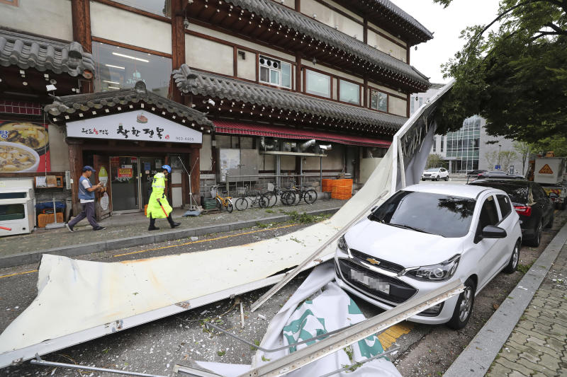 A vehicle is damaged by a fallen signboard from a building as Typhoon Lingling brings strong wind and rain in Seoul, South Korea, on Saturday. (AP photo)