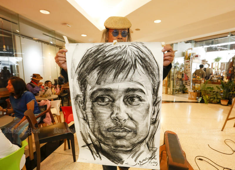 An artist shows the picture of Karen rights activist Porlajee 'Billy' Rakchongcharoen in drawing which is on display at the Bangkok Art and Culture Centre. (Photo by Pattarapong Chatpattarasill)