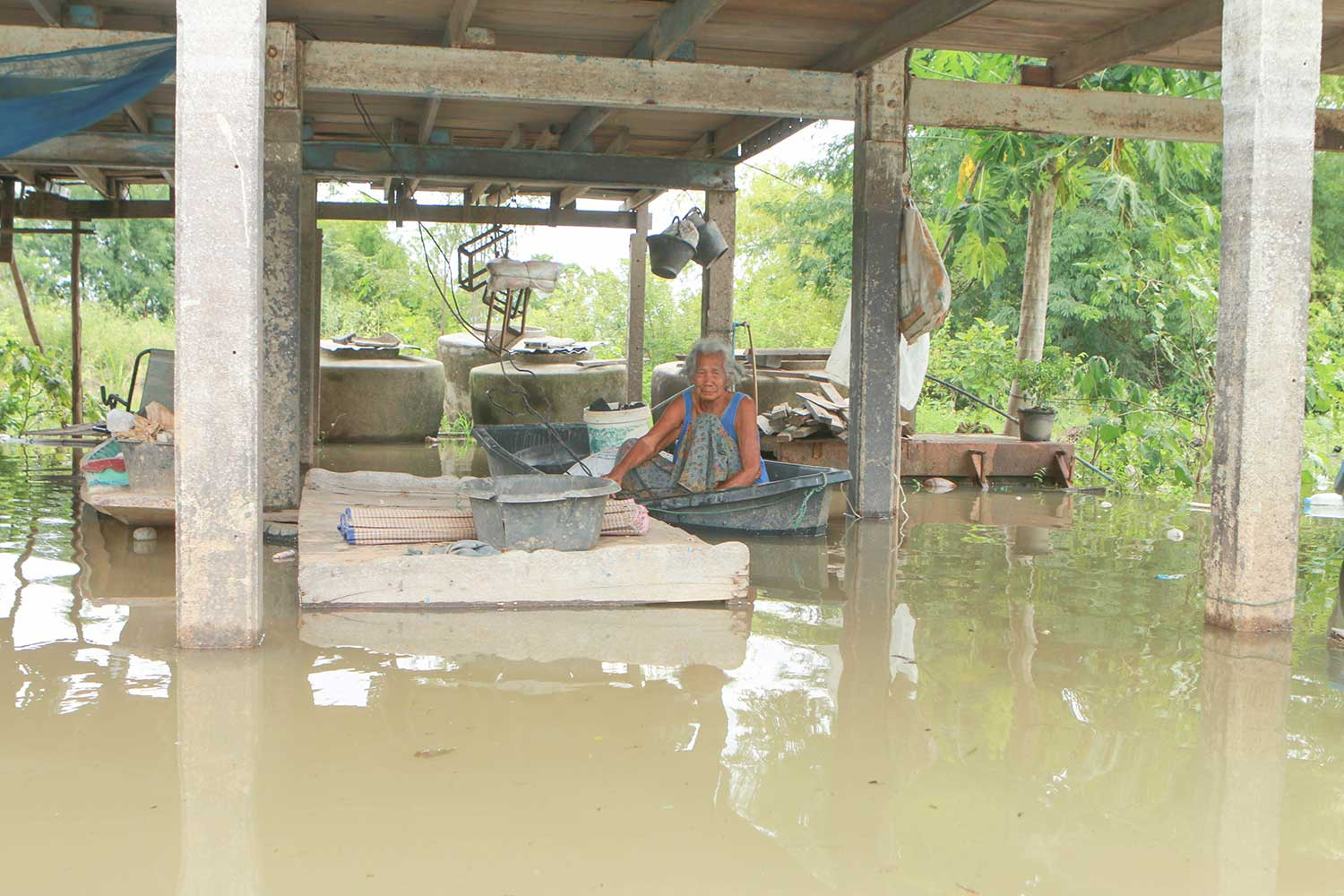 A woman uses a small boat to get around her flooded village in Chum Saeng district of Nakhon Sawan province on Monday. (Photo by Chalit Phumpuang)