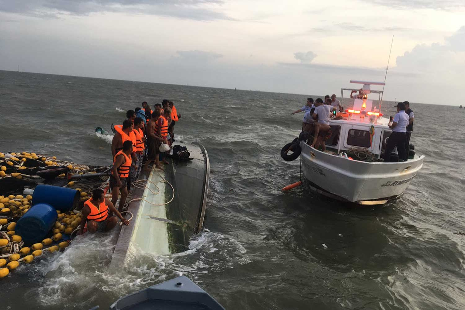 A fishing boat carrying 23 crew members capsizes at the mouth of the Chao Phraya River in Samut Prakan province on Monday evening. The boat was later salvaged on Tuesday morning and one crewman who was drowned and went missing was found trapped inside. (Photo by Sutthiwit Chayutworakan)