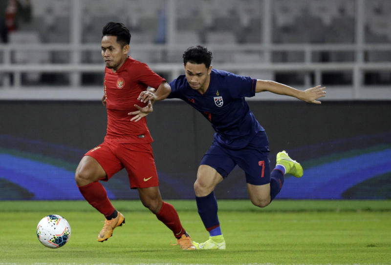 Indonesia's Andik Vermansah (left) fights for the ball with Supachok Sarachat during the World Cup Group G Asia qualifying soccer match at Gelora Bung Karno Stadium in Jakarta on Tuesday. (AP photo)