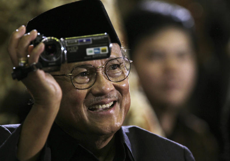 Former Indonesian president B.J. Habibie films the crowd as he sits in the audience to hear then US president Barack Obama's speech at the University of Indonesia in Jakarta on Nov 10, 2010. (AP photo)