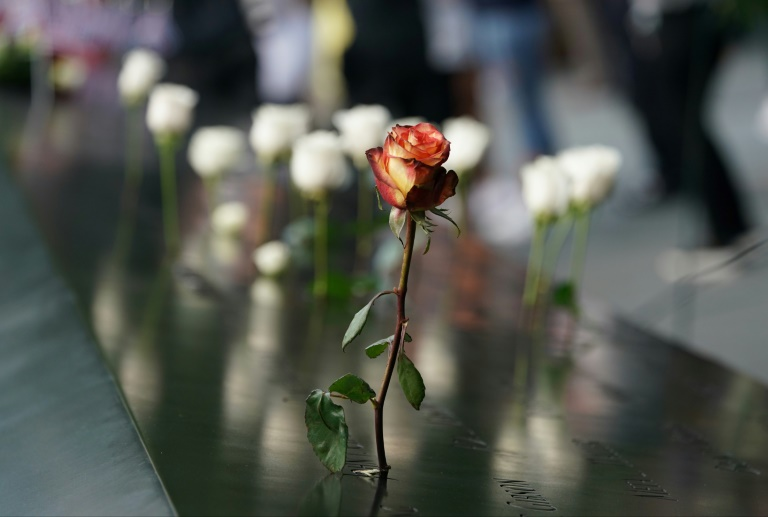 People leave flowers during the September 11 Commemoration Ceremony at the 9/11 Memorial at the World Trade Center