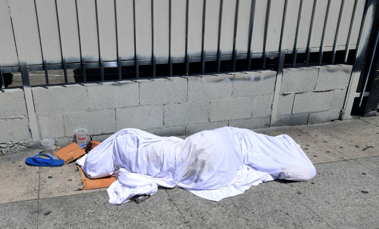 A homeless person' sleeping under a sheet on a sidewalk in Los Angeles on Sunday, home to one of the nation's largest homeless populations.