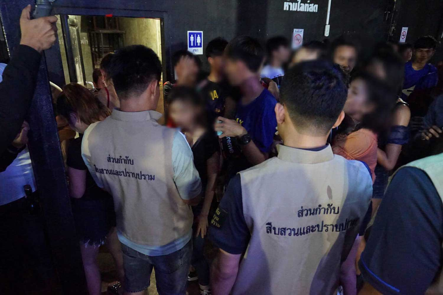 Officials round up patrons, many of them underage, during a raid on Club64 Pub & Restaurant in Sukhothai early Saturday. (Photo from the Facebook page of the Department of Provincial Administration's investigation and suppression office)