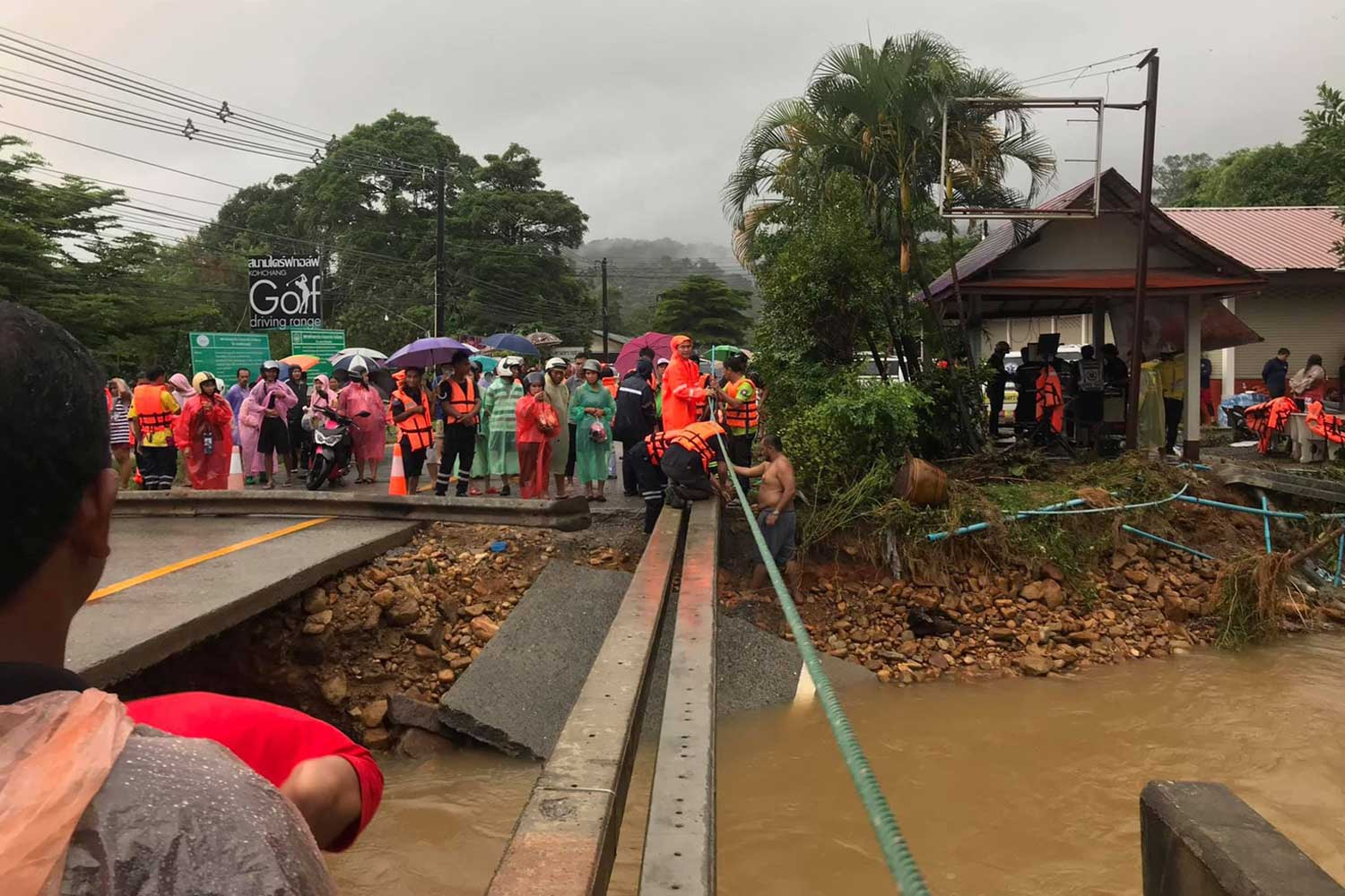 Volunteers secure a rope as a hand-hold for tourists to walk across Khlong Plu canal on a temporary footbridge of power poles, on Koh Chang island in Trat province on Monday. The vehicle bridge was washed out by flooding caused by torrential rain. (Photo by Jakkrit Waewkraihong)
