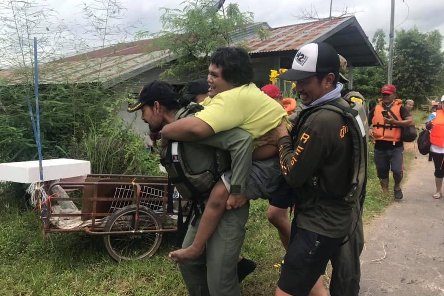Bin Bunluerit carries a handicapped person on his trip to help flood vticms in Ubon Ratchathani province on Saturday (Photo from บิณฑ์ บรรลือฤทธิ์ Facebook)