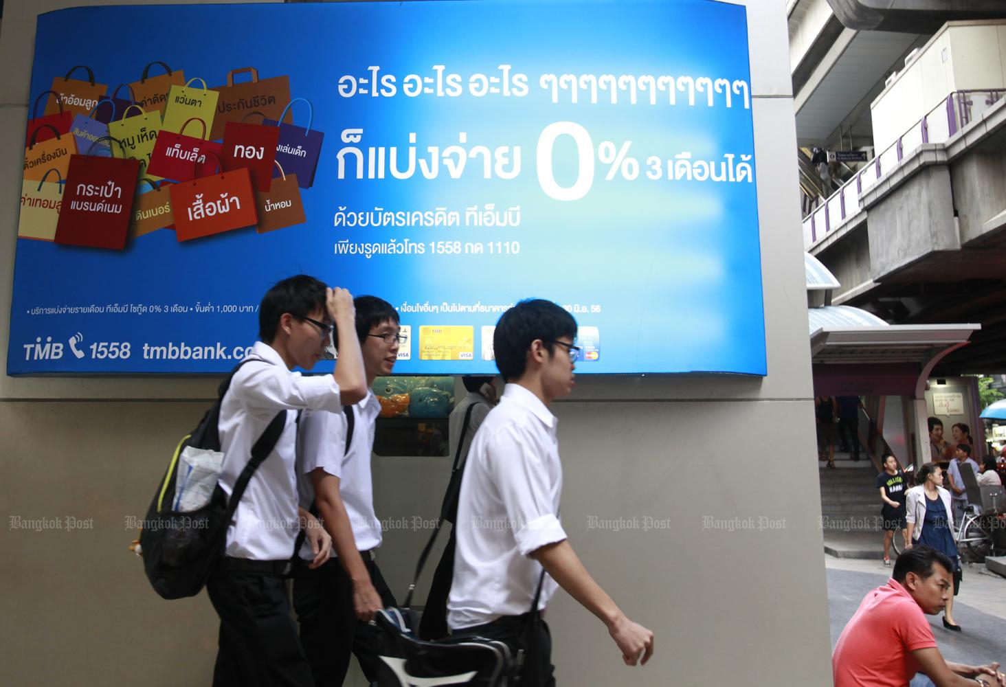 Pedestrians walk past a large sign promoting zero interest rates for instalment payments outside Siam Center in central Bangkok. (Photo by Thanarak Khunton)