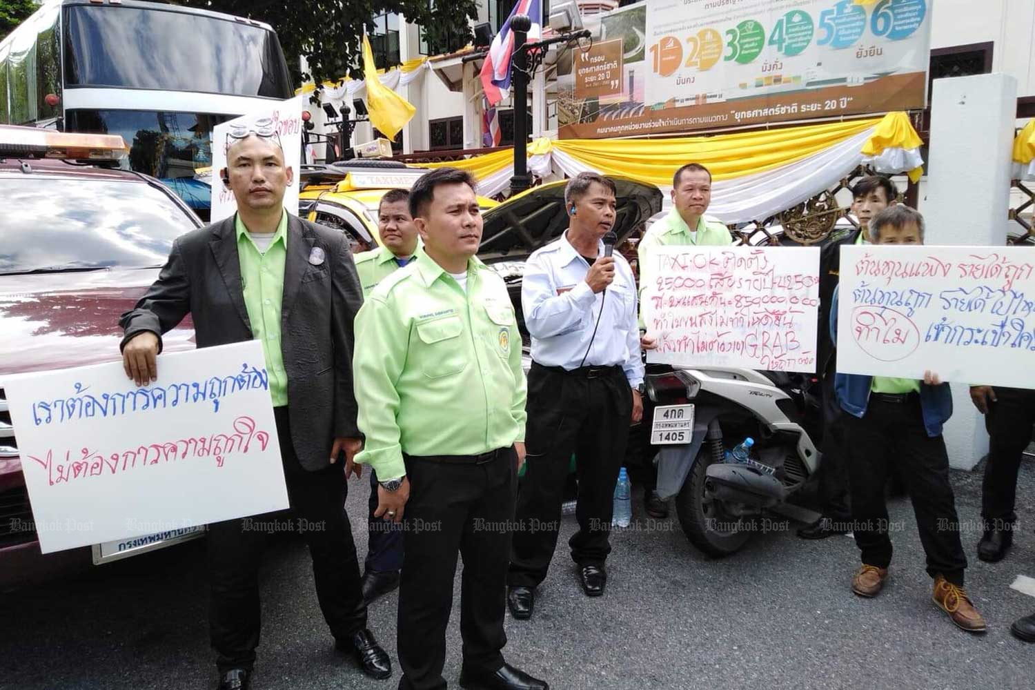 Worapol Kaemkhunthod, second left, leads a taxi drivers' rally at the Transport Ministry in Bangkok on Tuesday. (Photo by Thodsapol Hongthong)