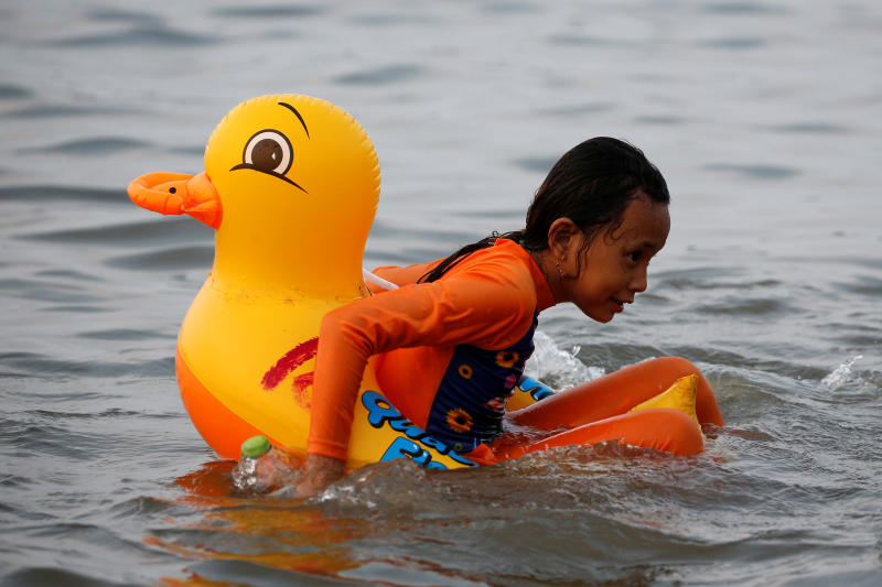 A girl plays with an inflatable duck as she swims during the first day of the Muslim holiday Eid al-Fitr at Ancol beach in Jakarta, Indonesia, June 6, 2019. (Reuters file photo)