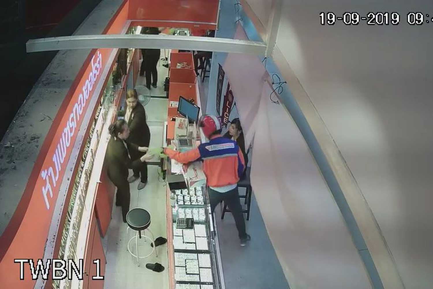 A man in a Thailand Post uniform robs the Aurora Gold and Jewellery shop in Bang Phli district of Samut Prakan on Thursday morning. (Photo supplied)