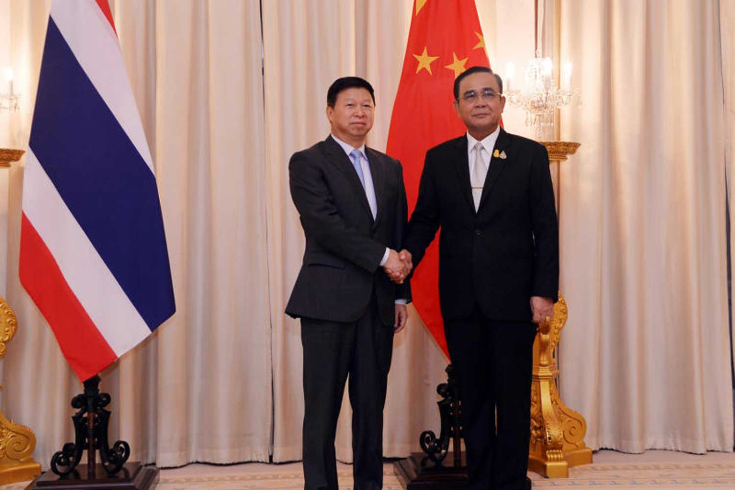 Prime Minister Prayut Chan-o-cha shakes hands with Song Tao, Minister of the International Department of the Central Committee of the Communist Party of China, at Government House on Thursday. (Government House photo)