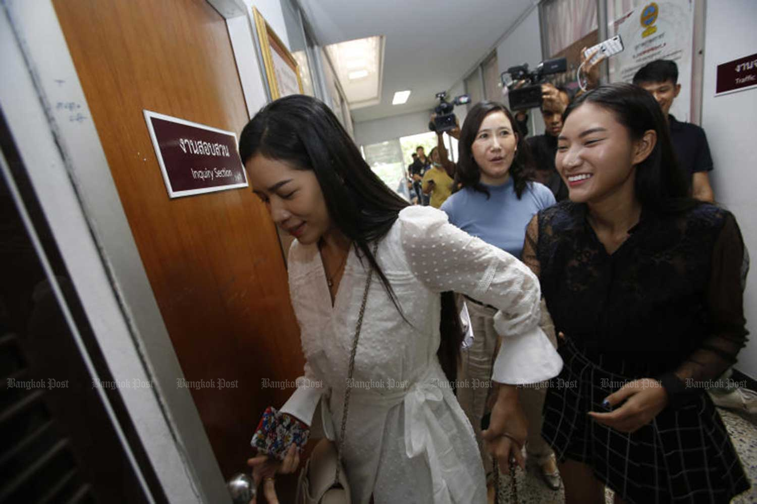 Product presenters who are friends of Thitima Noraphanpiphat arrive at the Bukkhalo police station on Thursday to discuss the case with investigators. (Photo by Pornprom Satrabhaya)