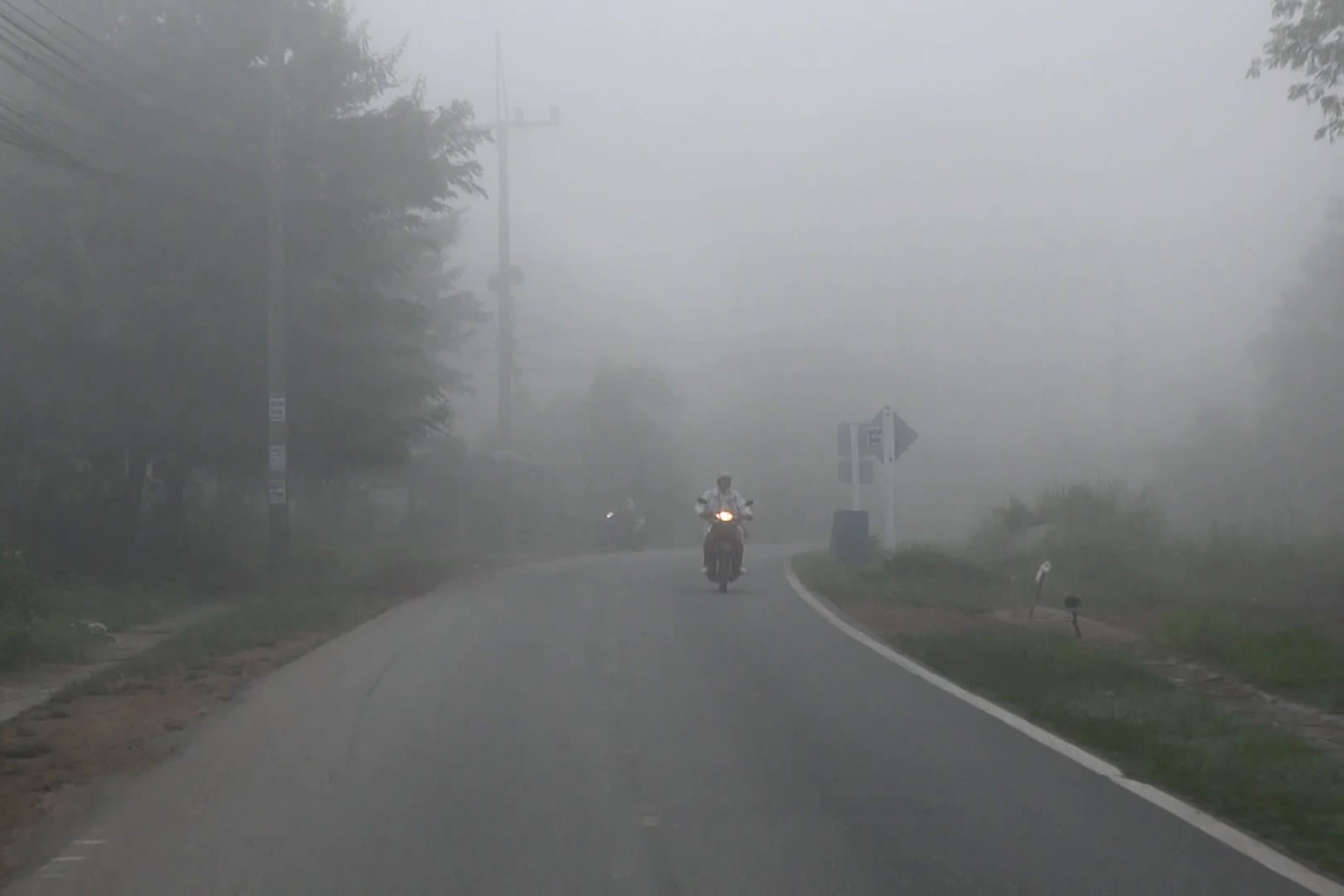 A motorcyclist in Hat Yai district in Songkhla rides on a road shrouded by haze from Indonesian forest fires. (Photo by Assawin Pakkawan)