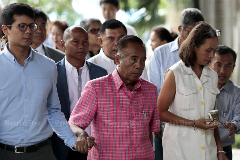 Red-shirt member Veerakarn Musikapong (centre) arrives at the Criminal Court on Monday for a ruling on their roles in the violent protest outside the home of the late Privy Council president, Prem Tinsulanonda, in 2007. (Photo by Patipat Janthong)