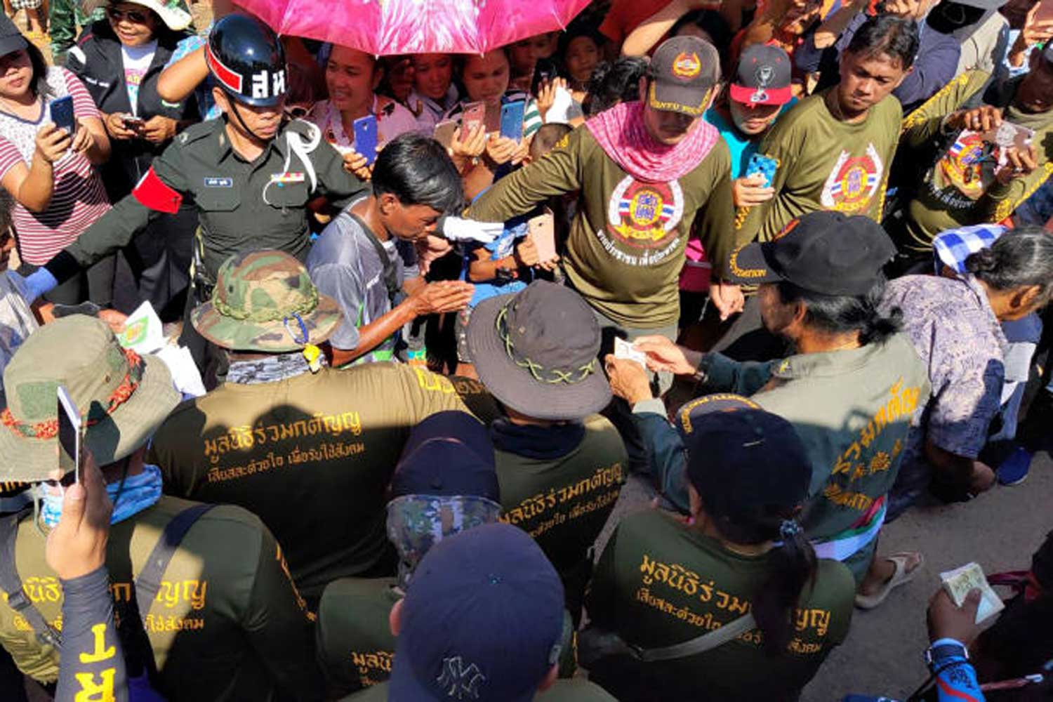 Flood victims are receiving cash from actor and rescue volunteer Bin Bunluerit, right, in Warin Chamrap district, Ubon Ratchathani province, on Sept 17. (Army photo)