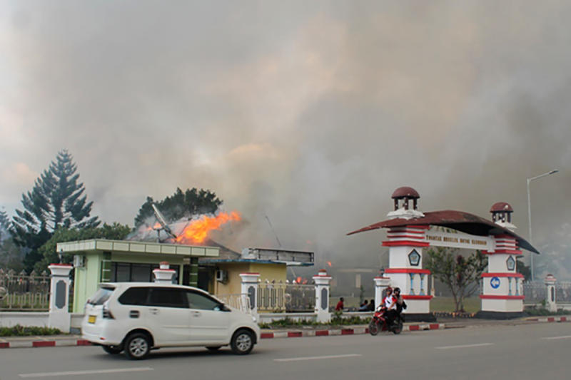 A car passes the governor's office building in Jayawijaya burned during a protest in Wamena, Papua, Indonesia, on Mondah. (Antara Foto/Marius Wonyewun/ via REUTERS)