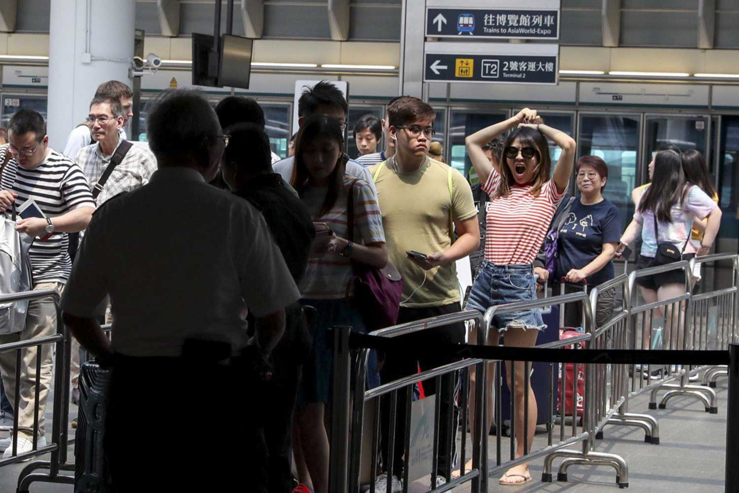 Travellers queue to go through a security check before entering Hong Kong International Airport earlier this month following anti-government protests. (South China Morning Post photo)