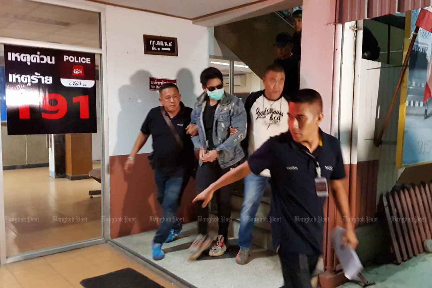 Police escort Rachadech Wongtabutr, 25, into a room at Metropolitan Police Division 8 in Bangkok early Wednesday morning after his arrest in relation to the death of product presenter Thitima
