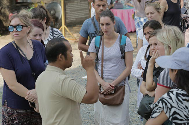 A tour guide shows tourists around the Angkor Archaeological Park. Tour guides can now obtain e-certificates from the Ministry of Tourism. (Khmer Times photo)