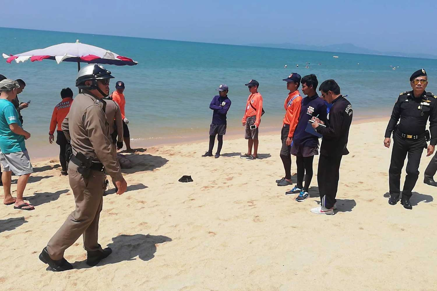 Police with the body of the Kazakhstani woman, 78, at Jomtien beach, near  Pattaya town, in Chon Buri on Thursday morning. (Photo by Chaiyot Pupattanapong)