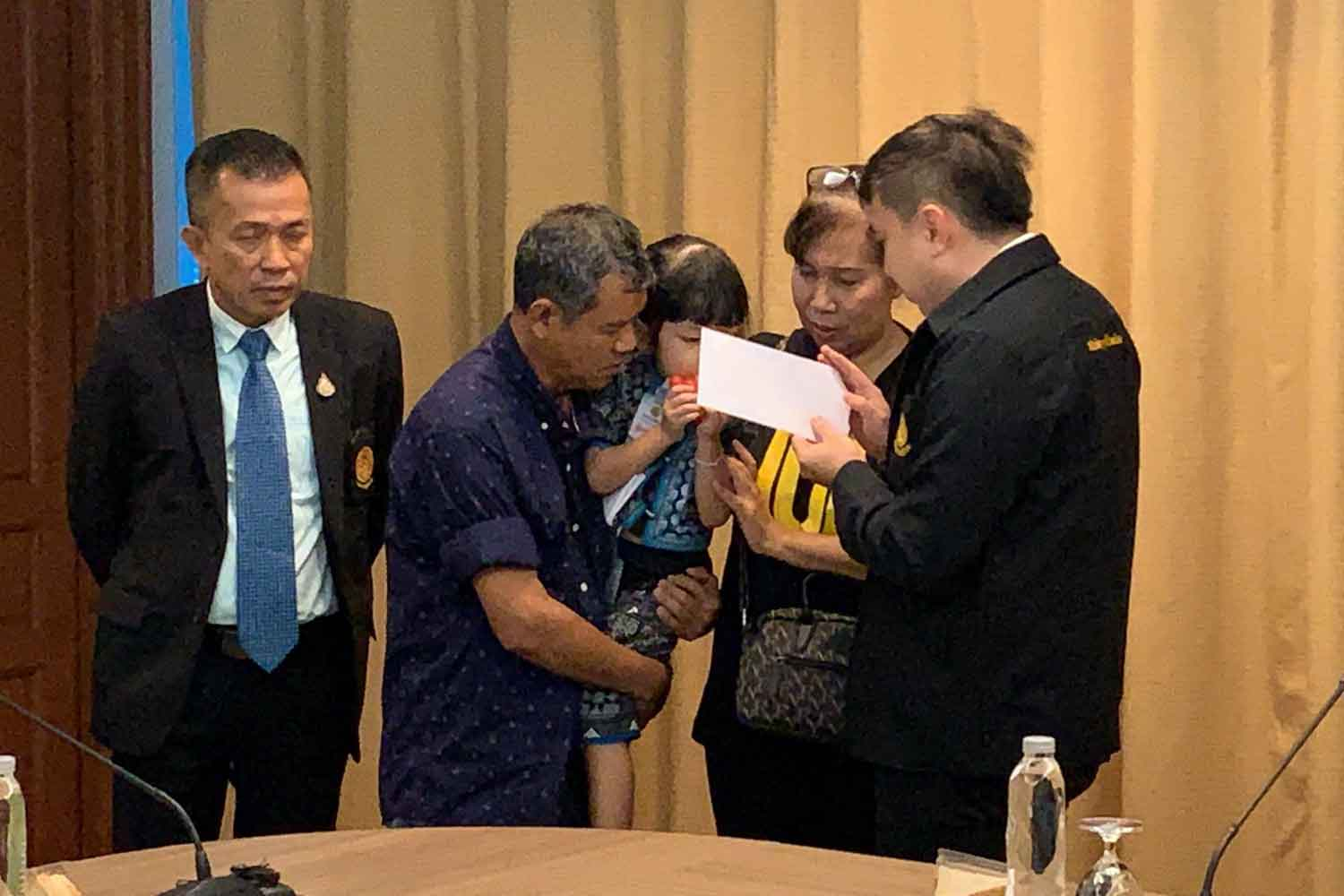 The parents of deceased product presenter Thitima Noraphanpiphat, with her three-year-old child, file their request for a second autopsy at the Justice Ministry in Bangkok on Thursday. (Photo supplied)
