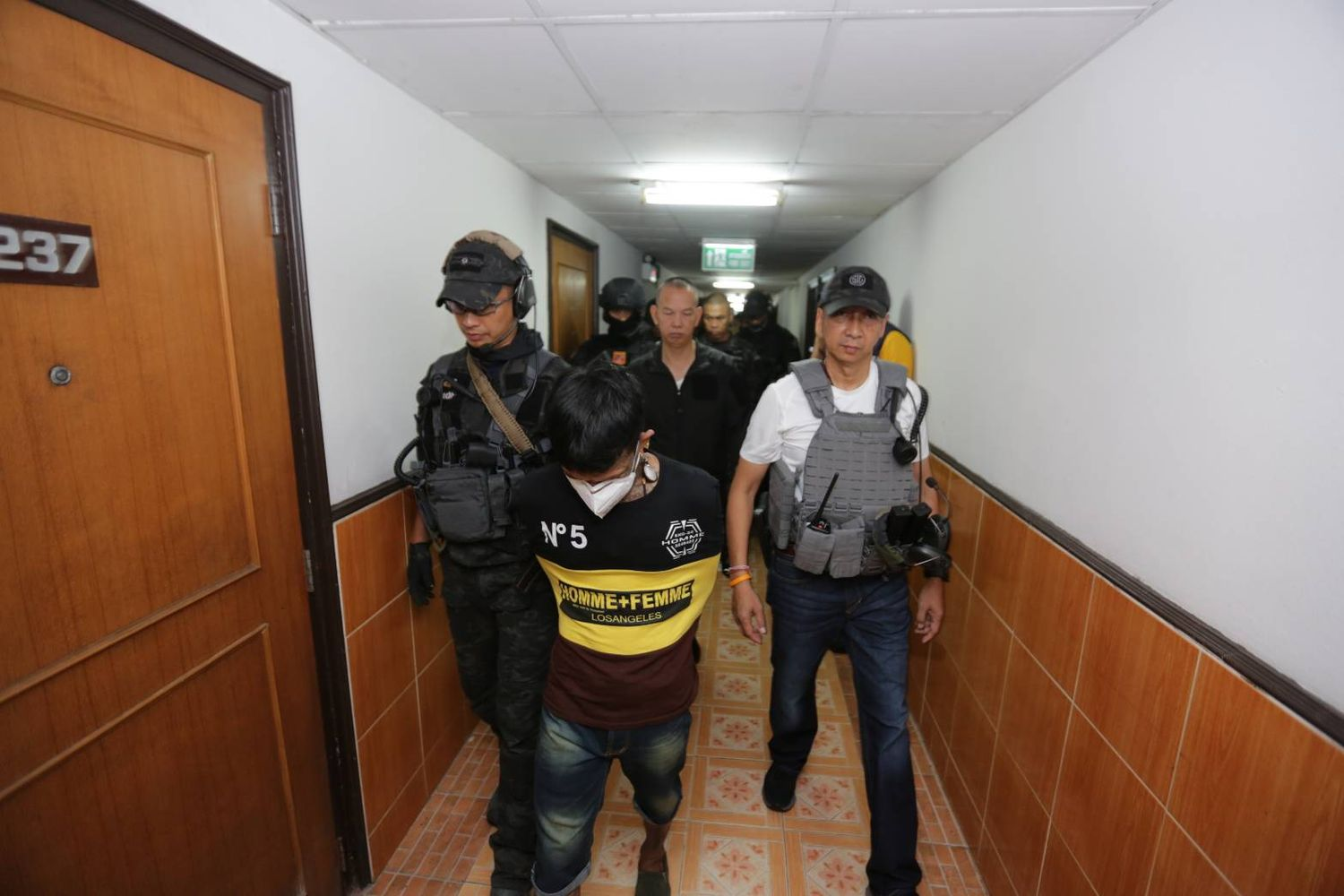 Anti-human trafficking police officers take a suspect into custody after a crackdown on a hotel in Bangkok's Hua Lamphong area. (Photo supplied by Wassayos Ngamkham)