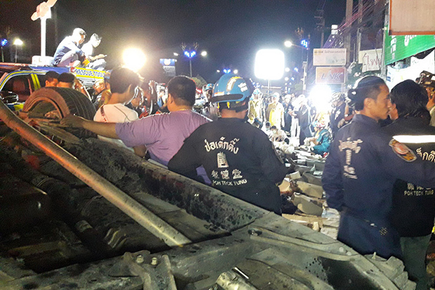 Rescue volunteers help people in a pickup truck that overturned in Bang Phli district of Samut Prakan on Sunday. (Photo by Sutthiwit Chayutworakan)