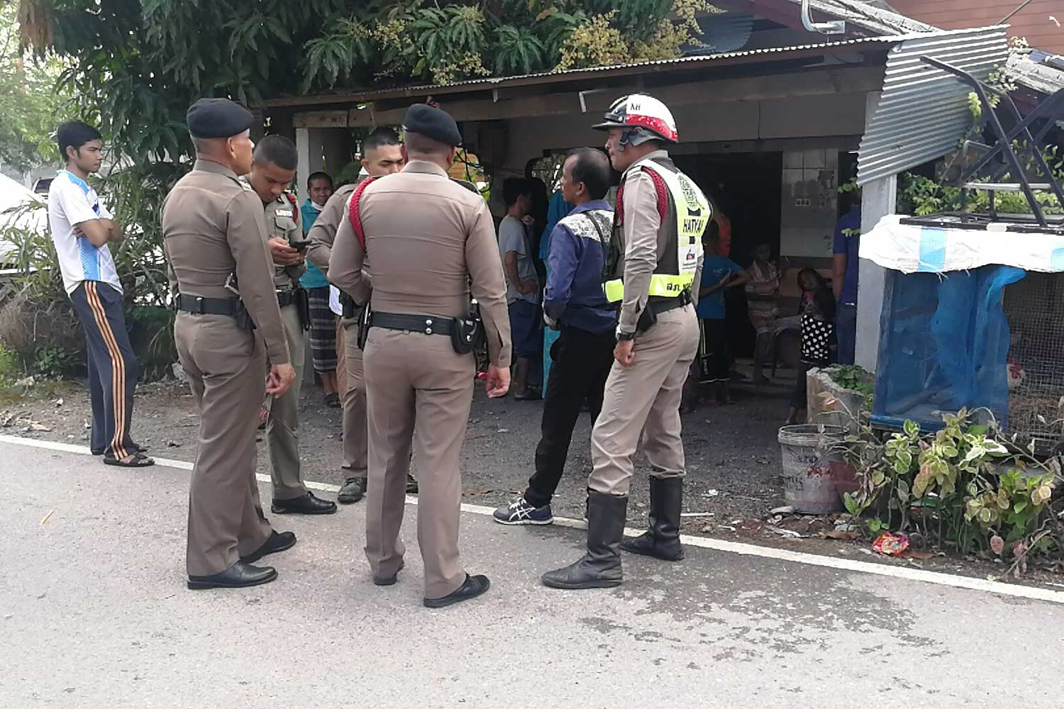 Police stand outside the house in Hat Yai district of Songkhla where Abdulloh Sanbuatboo was foud dead on Sunday. (Photo by Assawain Pakkawan)