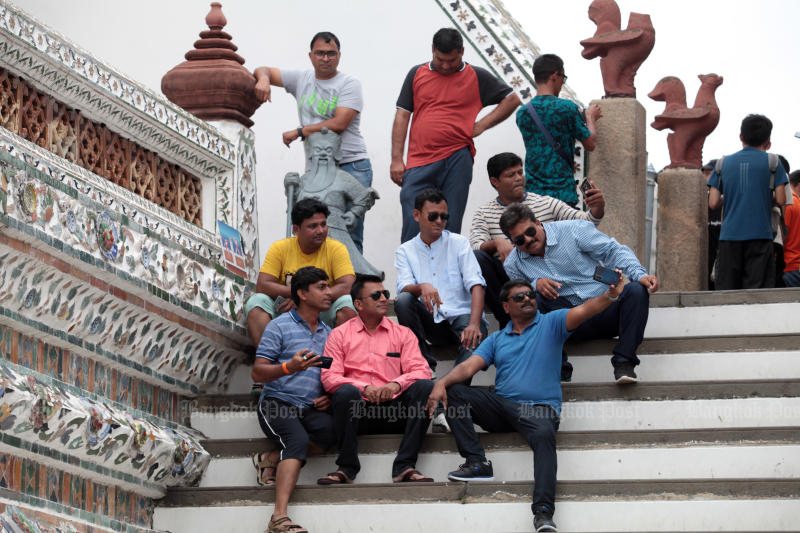 Foreign tourists pose for photos at Wat Arun, or the Temple of Dawn. (Photo by Chanat Katanyu)