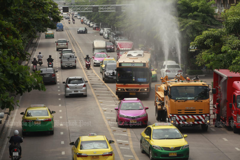 A truck sprays water to reduce the ultra-fine PM 2.5 pollutants in the air in Bang Sue district on Tuesday. The district was the third worst polluted area. (Photo by Pornprom Satrabhaya)