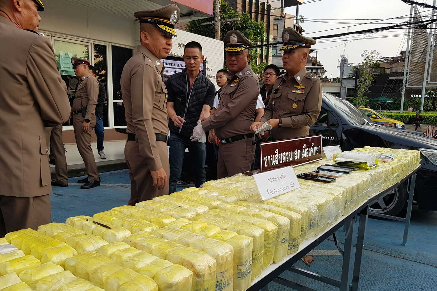 Pol Lt Gen Montri Yimyaem, centre, commander of the Provincial Police Region 2, and other senior police look at the packs of speed pills and crystal methamphetamine seized from five suspects in Chon Buri and three other provinces, prior to the news conference on Tuesday evening. (Photo by Chaiyot Pupattanapong)