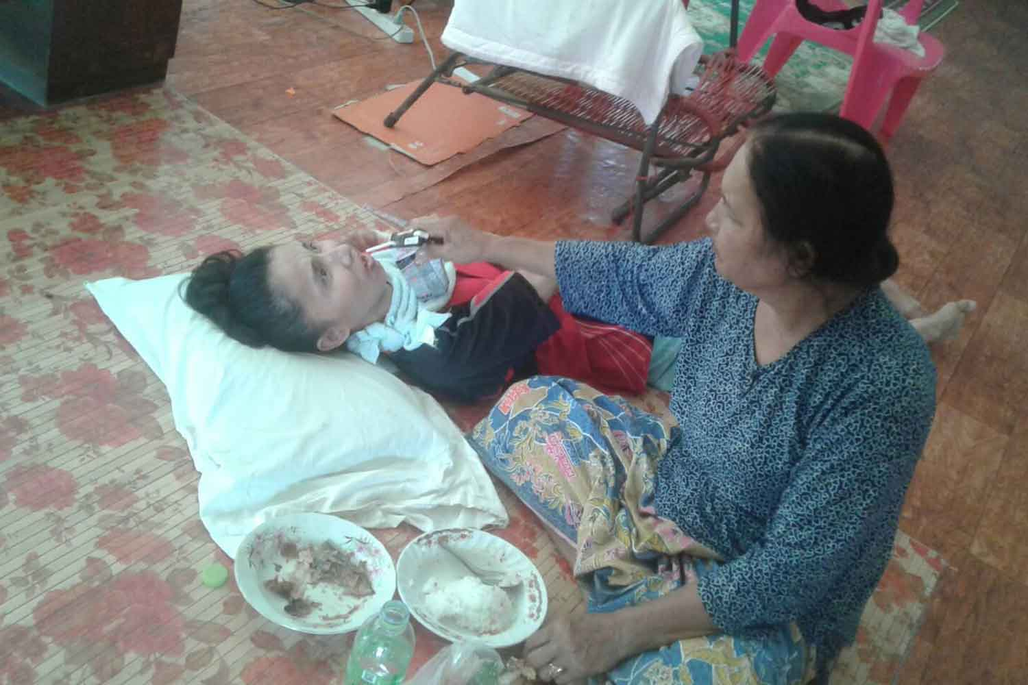Koliyoh Sriyaphai (right), 63, has been taking care of her daughter Wanna, now 37, for 17 years at their home in Muang district, Nakhon Si Thammarat, after she had been set ablaze by an estranged boyfriend who was arrested on Wednesday for the alleged crime. (Crime Suppression Division photo)