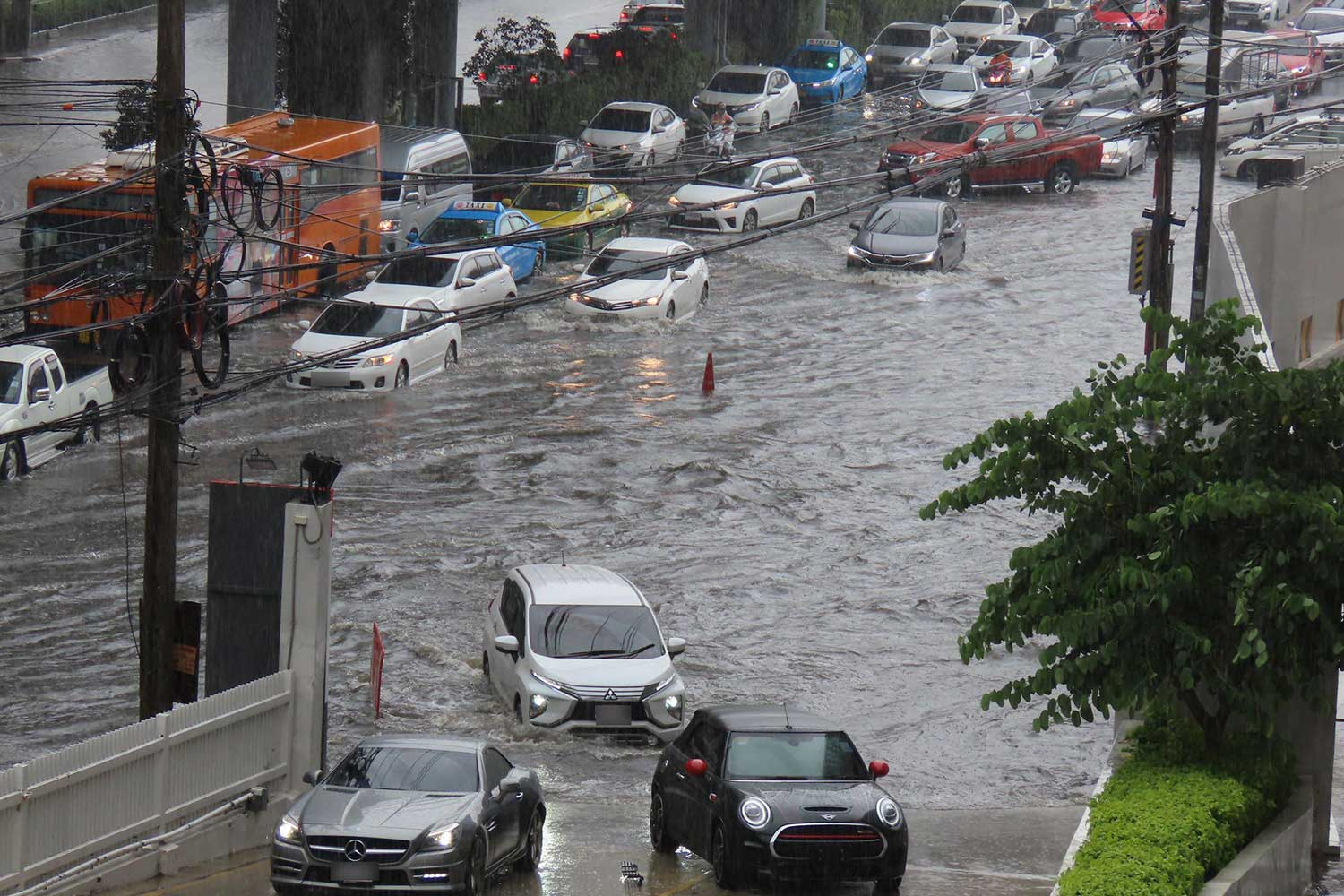 Cars navigate a flooded road at the Bang Na intersection after heavy rain hit several areas in Bangkok on Saturday. (Photo from @js100radio Facebook page)