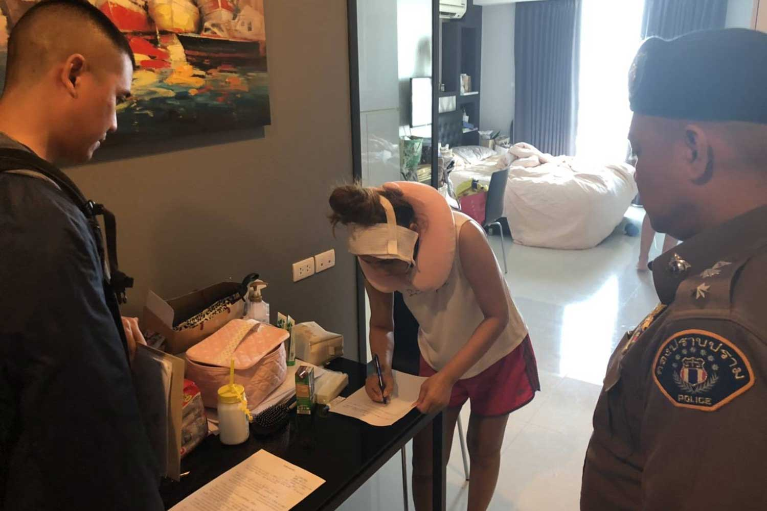 Fashion model Sriwipha Wattanawansap signs papers at her condominium as police officers look on following her arrest on fraud charges. (Crime Suppression Division photo)