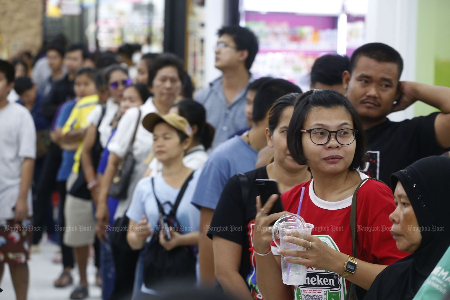 People wait to pay for goods using the government's 1,000-baht handouts aimed at stimulating the economy at the Prachachuen branch of Tesco Lotus hypermarket in Bangkok on Monday. (Photo by Pornprom Satrabhaya)