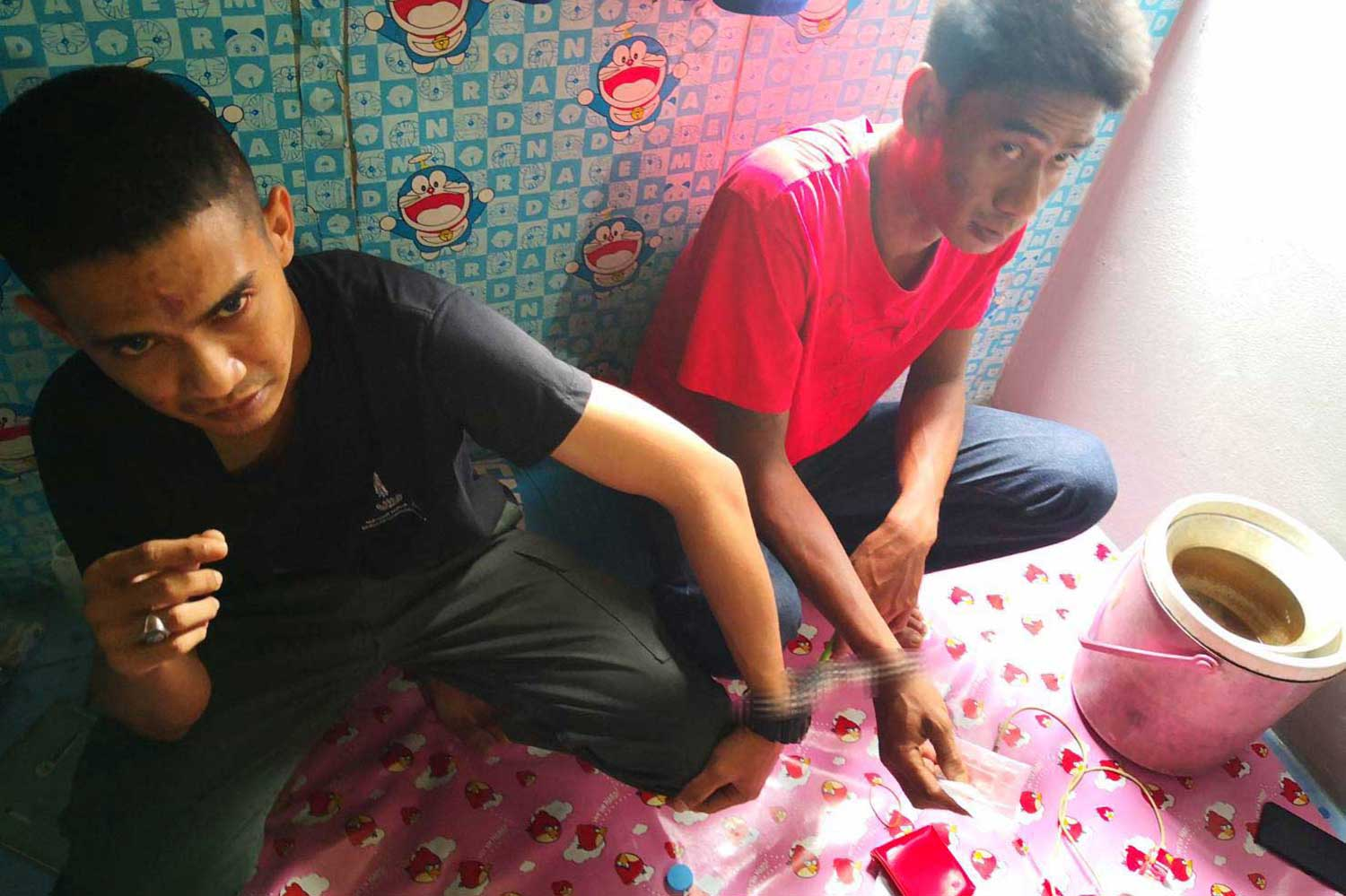 Pol Cpl Sanyalak Jandam,24, left, of Kapho police station in Pattani, and Piyapong Ruangchuay, 31, son of a local leader were arrested in possession of drugs at a house in Bang Klam district of Songkhla on Monday night. (Pool photos, via Assawin Pakkawan)