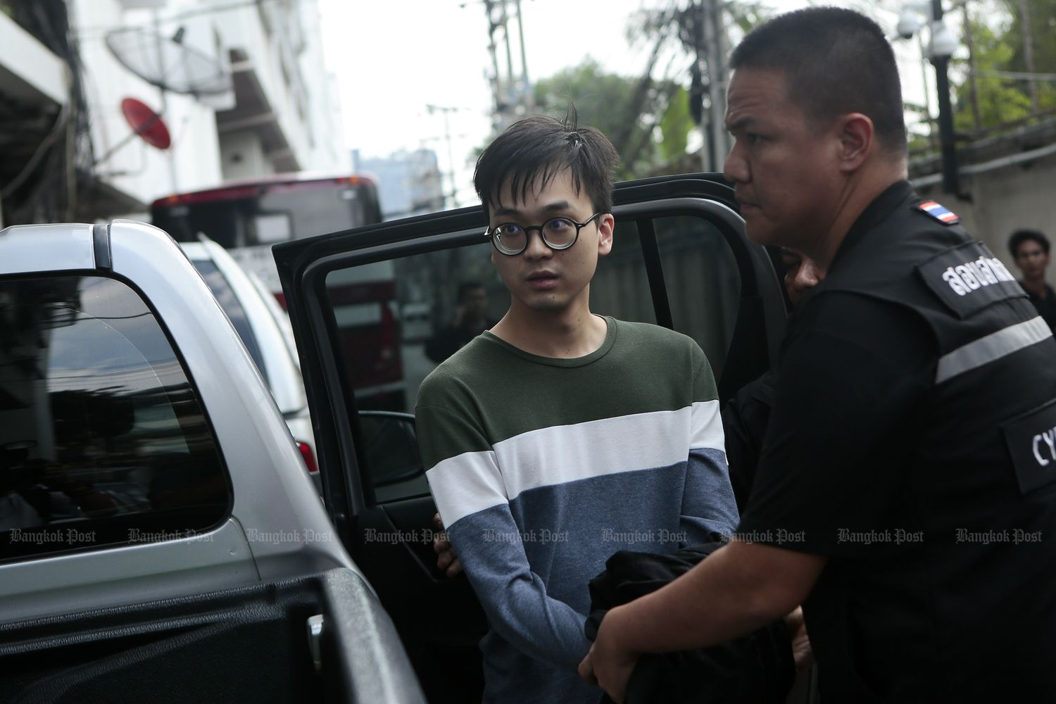 Karn Pongpraphapan, a pro-election activist, is brought to the Criminal Court in Bangkok as police seek to detain him on computer crime charges involving national security. (Photo by Patipat Janthong)