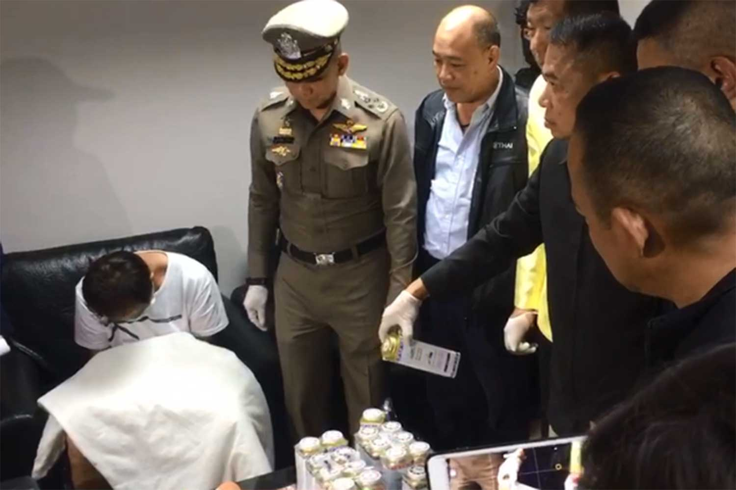 Officers seize heroin hidden in 18 tins of cooling powder from Chen Kuan Lin, 38, a Taiwanese man, left, as he was about to board a flight to his home country on April 26 this year. The Criminal Court on Wednesday sentenced him to life imprisonment. (Capture from a clip posted by @kaojorleuk.media Facebook page)