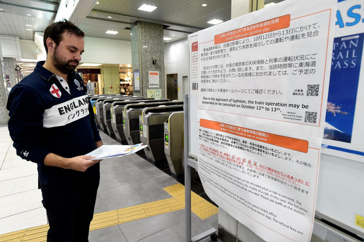 An England rugby supporter reads a travel warning posted at Hamamatsu railway station about Typhoon Hagibis and possible train suspensions and cancellations. (Photo: Reuters)