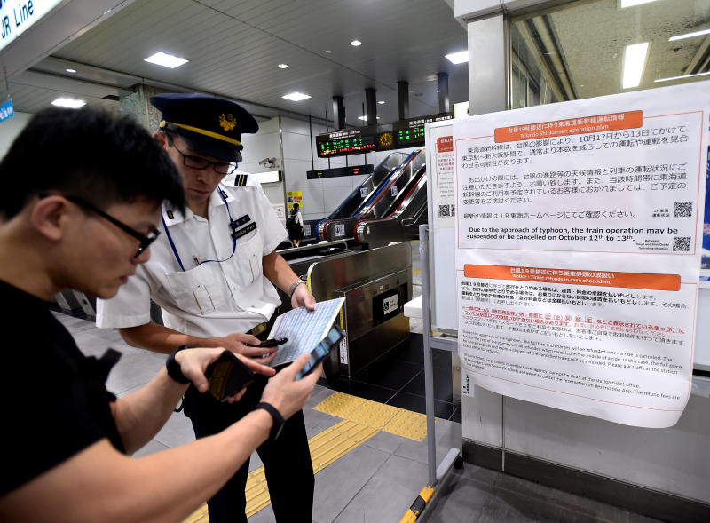 A Singaporean receives help from a Hamamatsu railway station staff member, next to a travel warning sign regarding Typhoon Hagibis and possible train cancellations or suspensions. Hamamatsu is located southwest of Tokyo. (Reuters photo)