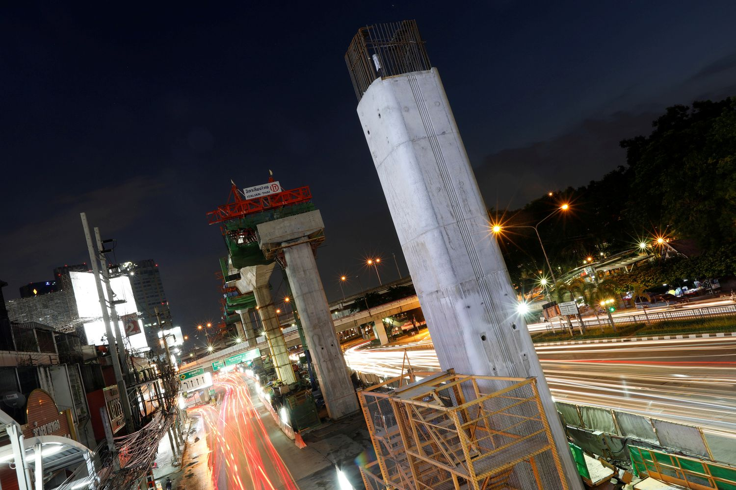 Cars pass a skytrain construction site in Bangkok on May 13 last year. (Reuters photo)