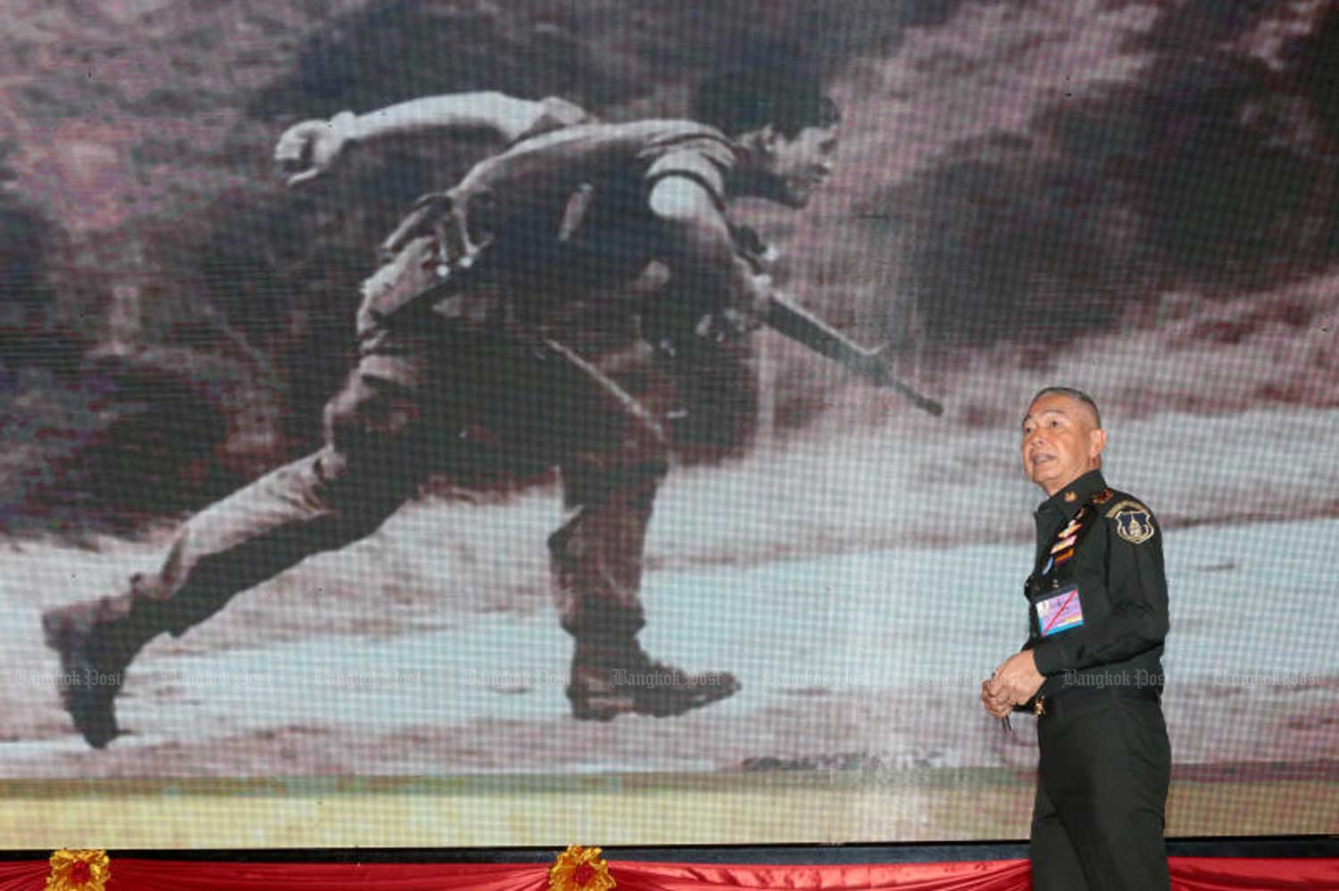 Army chief Gen Apirat Kongsompong describes how His Majesty the King fought against a communist force in Loei province in 1976, during his special lecture on national security at the Royal Thai Army headquarters in Bangkok on Friday. He is standing in front of a picture of the King when he was the Crown Prince, on the Loei battlefield. (Photo by Chanat Katanyu)