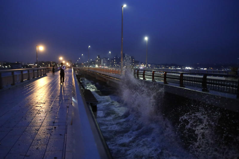 A man walks along the bridge connecting to Enoshima Island in Fujisawa, west of Tokyo, on Friday, as Typhoon Hagibis approaches the area. (AP photo)