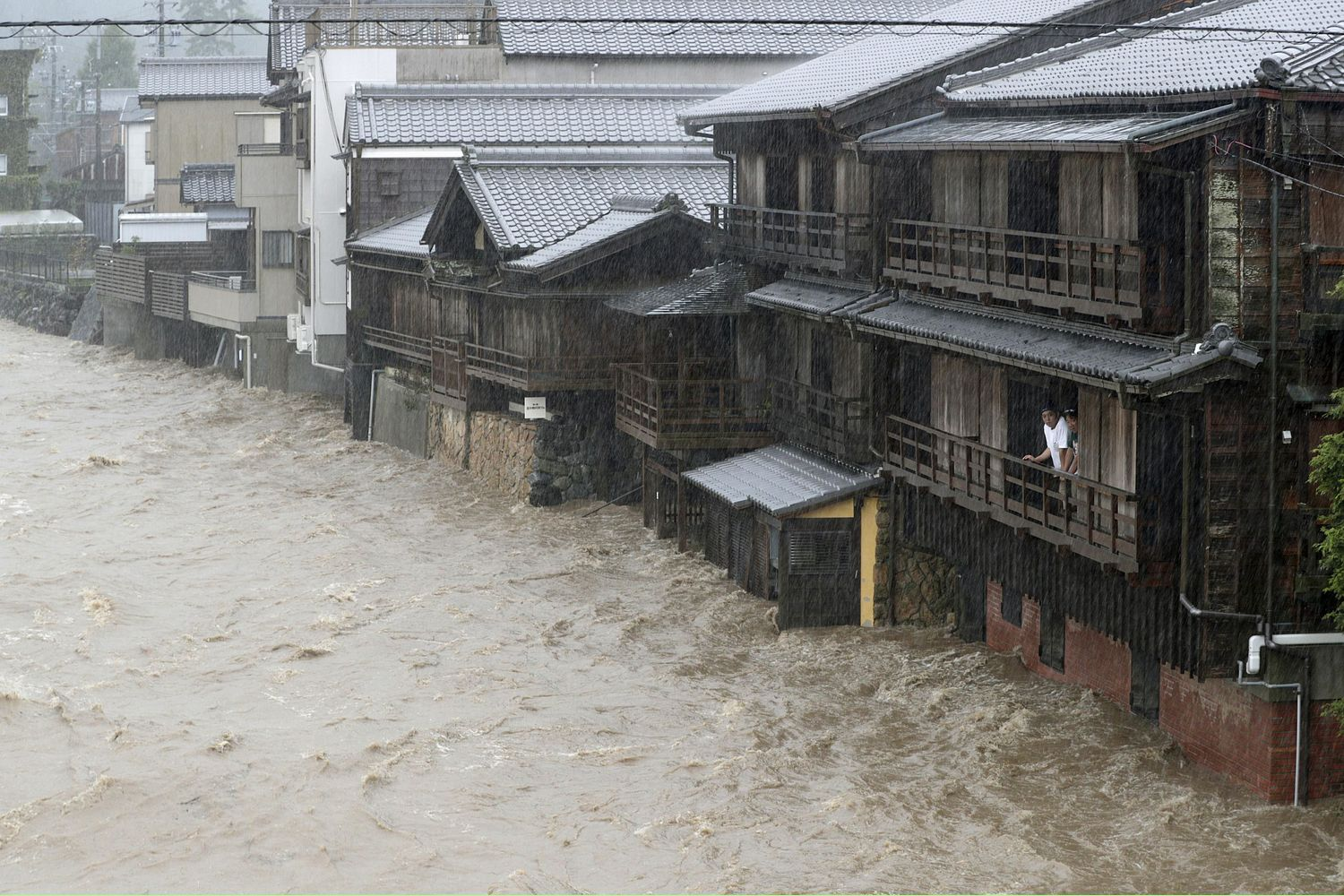 Men watch as the rain-swollen Isuzu River surges past houses in Ise in central Japan on Saturday. (Kyodo Photo)