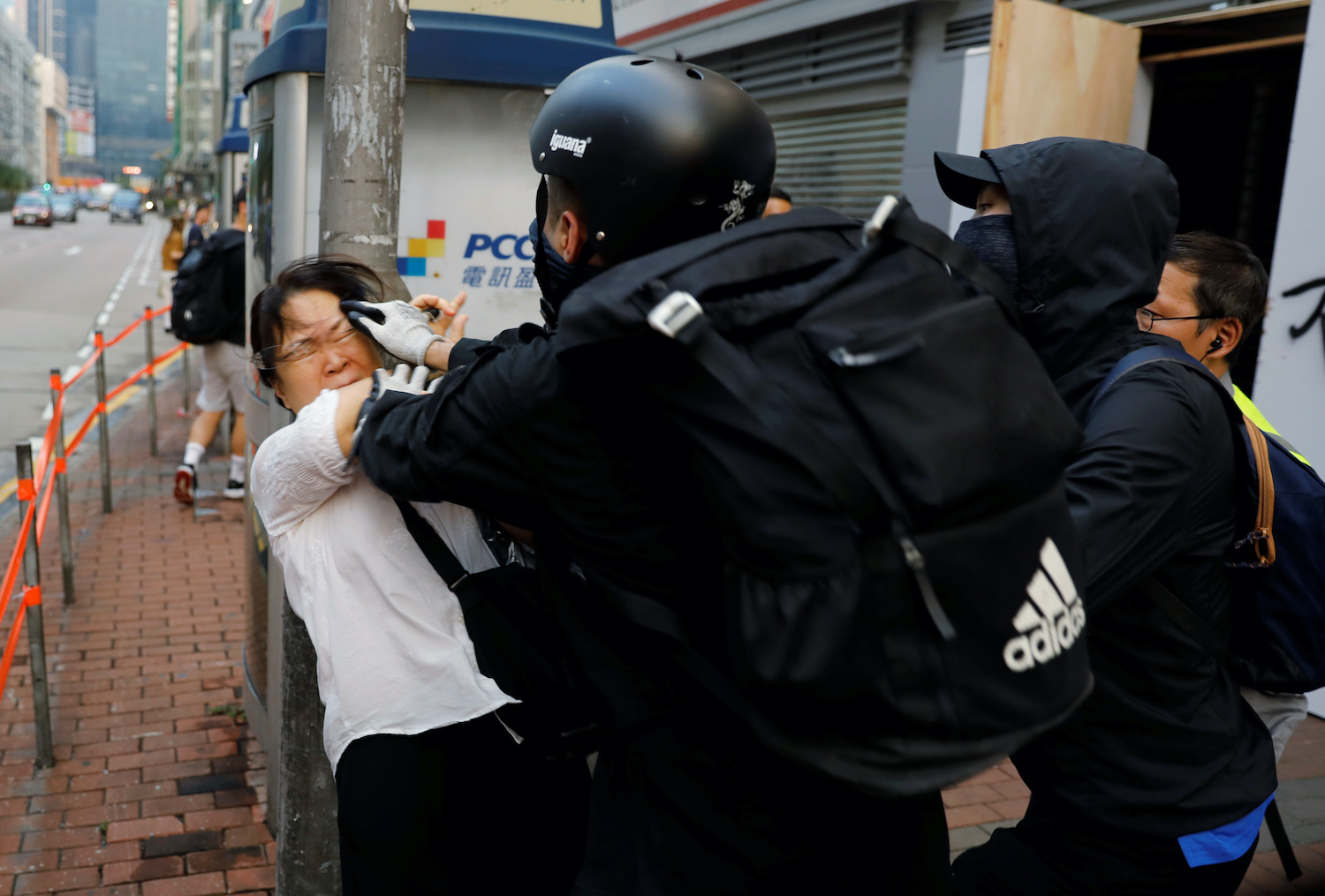 An anti-government demonstrator scuffles with a woman after she tried to remove his mask in Hong Kong on Saturday. (Reuters Photo)